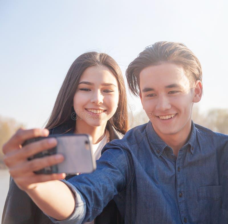 Um par anos asiáticos dos adolescentes velhos tomam um selfie no telefone, têm o divertimento, melhores amigos fotografia de stock