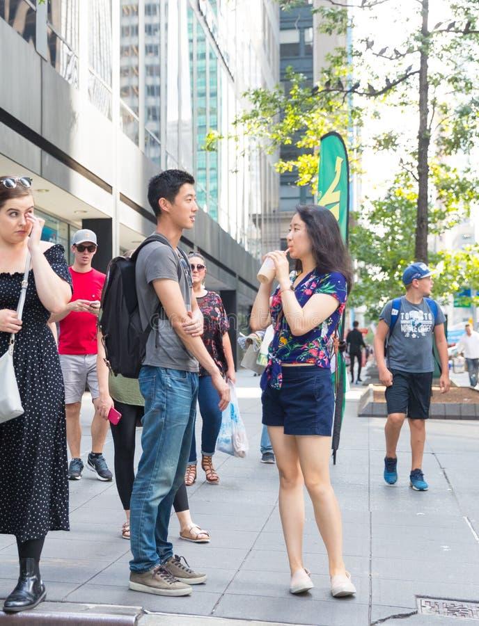 Um par asiático que conversa na rua em New York City imagem de stock