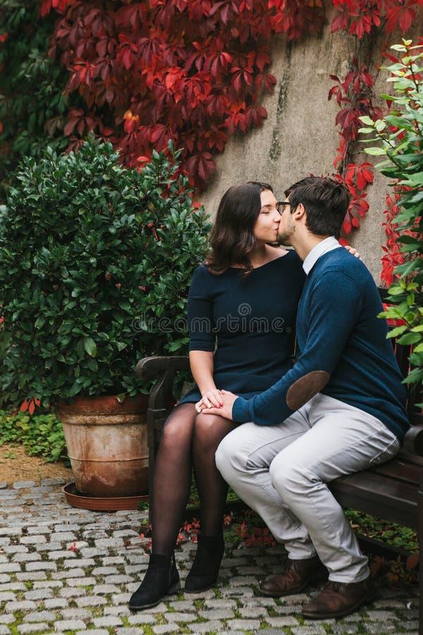 Um par bonito novo loving de estudantes de Europa que senta-se em um banco e que beija em um parque no outono fim foto de stock