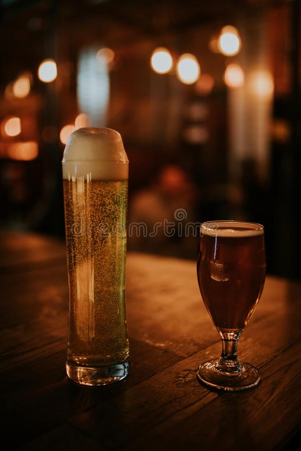 Um par cervejas diferentes em uma tabela de madeira imagens de stock royalty free