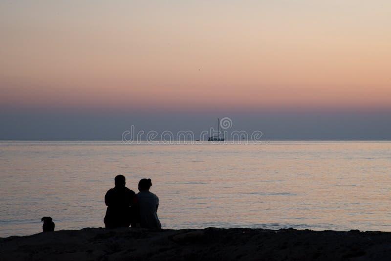 Um par com um cão que olha o nascer do sol na imagem horizontal da costa de mar imagens de stock royalty free