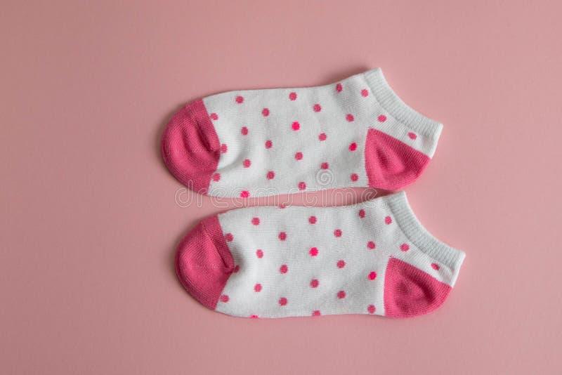 Um par das peúgas brancas para crianças com peúgas cor-de-rosa e saltos, com pontos cor-de-rosa, em um fundo cor-de-rosa Peúgas p fotos de stock