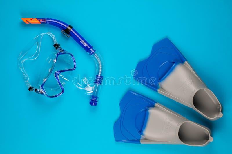 Um par de óculos de proteção nadadores ao lado de um par de aletas, no fundo azul ilustração royalty free