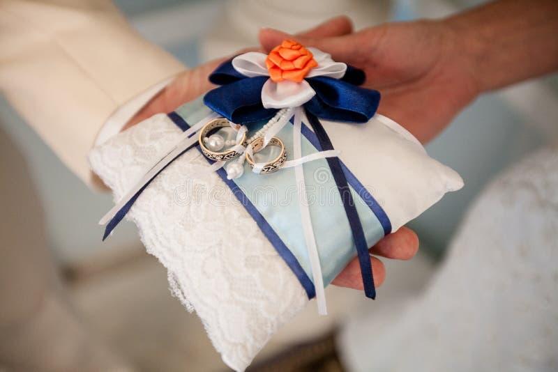 Um par de alianças de casamento em um descanso branco imagem de stock royalty free