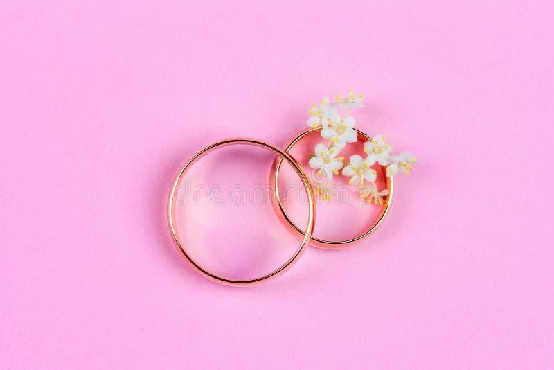 Um par de alianças de casamento de ouro e de flores brancas pequenas em um anel em um fundo cor-de-rosa, vista superior fotografia de stock