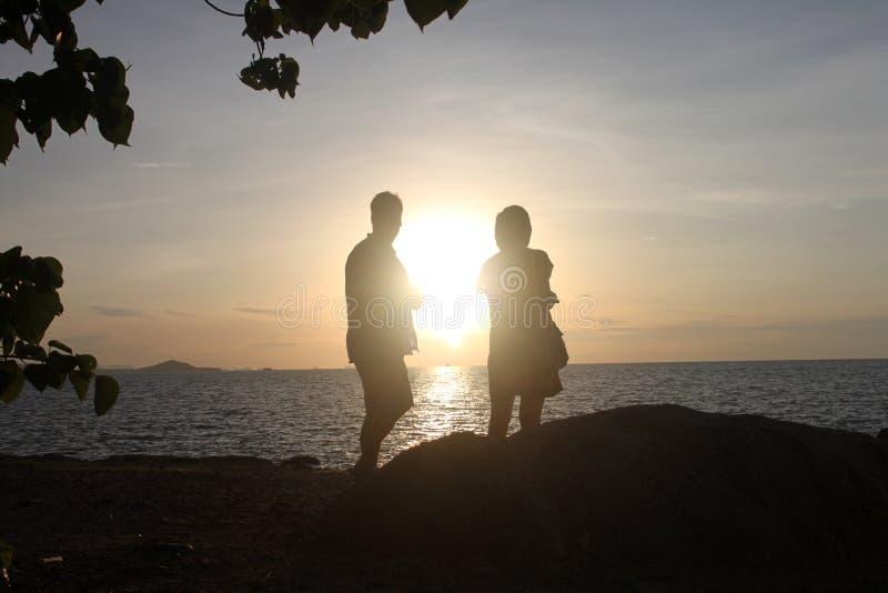 Um par de amantes considera um trajeto do sol do mar com navio e as folhas distantes imagens de stock