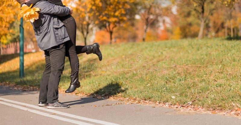 Um par de amor - um homem e uma mulher - passa o tempo junto no parque do outono, abraçando imagem de stock