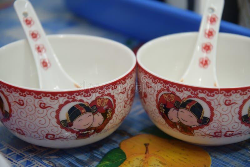Um par de bacias e de colheres cerâmicas idênticas para a sopa glutinosa dos riceballs do dia do casamento feito sob encomenda ch foto de stock royalty free