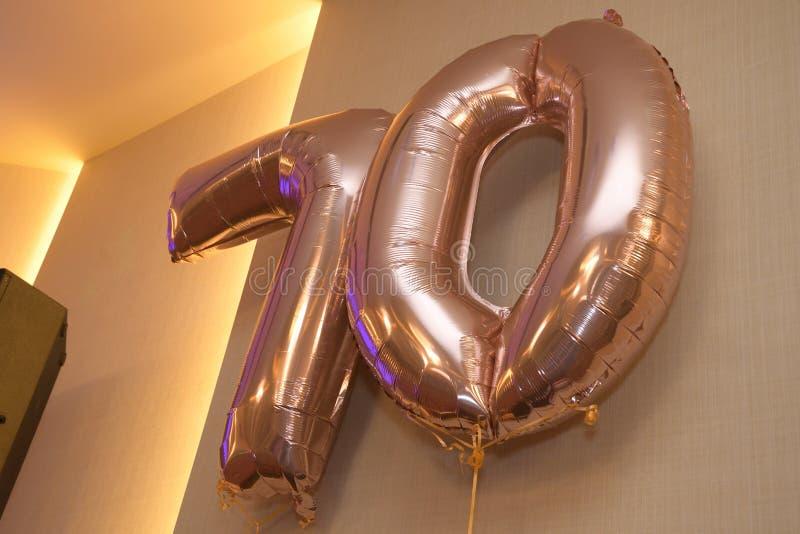 Um par de balões insuflados de cor marrom-dourada metálicos arranjados para mostrar o número 70 imagens de stock royalty free