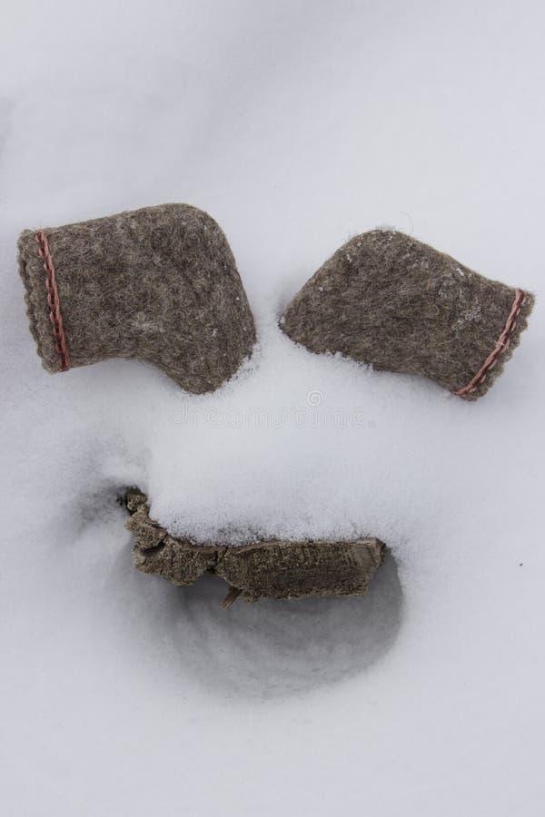 Um par de botas deixadas nos narizes brancos da neve abaixo de uma textura de madeira reminiscentes imagem de stock