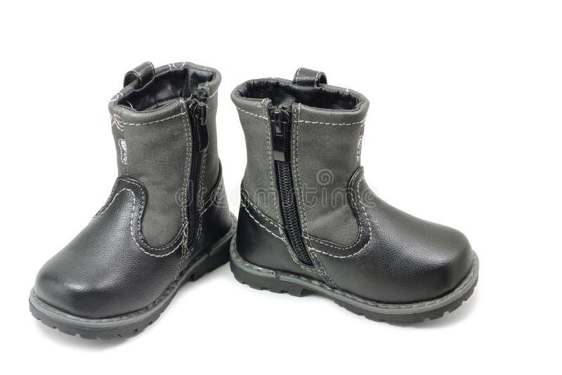 Um par de botas do inverno do ` s das crianças foto de stock