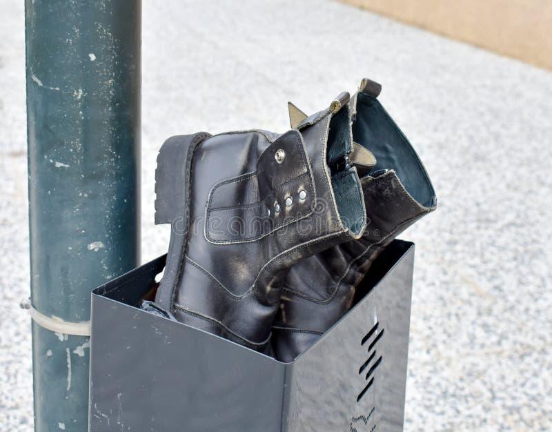 um par de botas pretas usadas feitas no couro preto abandonado em um escaninho preto Botas e escaninho em um cargo no passeio da  imagens de stock royalty free