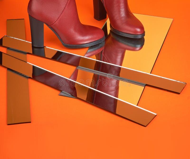 Um par de botas vermelhas altas de couro para mulheres em fundo amarelo-laranja com espelhos imagem de stock royalty free