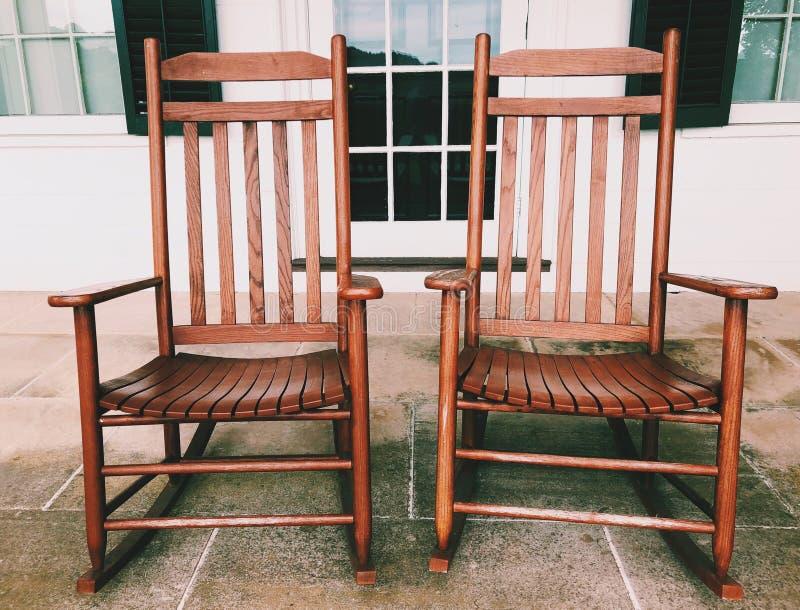 Um par de cadeiras de balanço de madeira velhas no patamar fotos de stock royalty free
