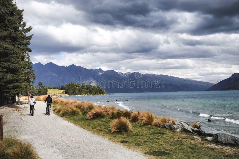 Um par de cavaleiros da bicicleta aprecia o cenário magnífico de Queenstown, Nova Zelândia imagens de stock royalty free
