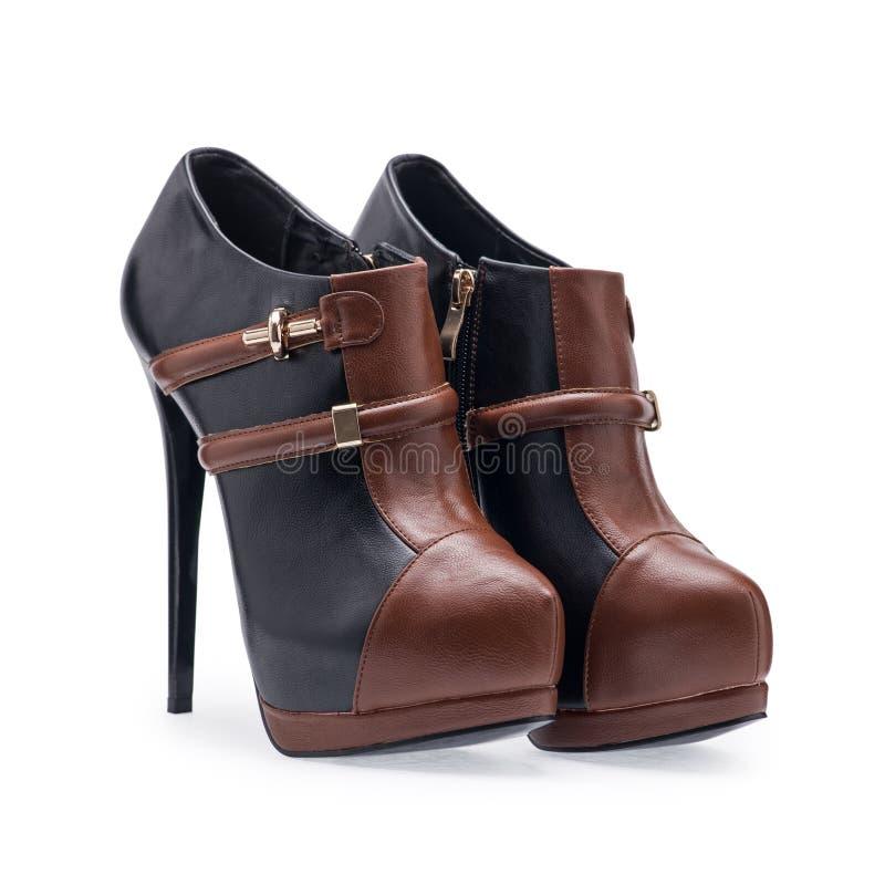 Um par de estiletes do preto e do marrom de sapatas das mulheres com uma correia decorativa fotografia de stock royalty free