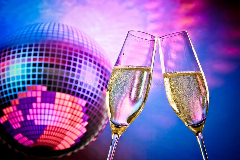 Um par de flautas de champanhe com bolhas douradas faz elogios no fundo azul e violeta efervescente da bola do disco imagens de stock royalty free