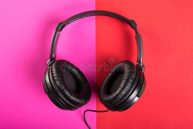 Um par de fones de ouvido pretos no fundo cor-de-rosa e vermelho imagens de stock