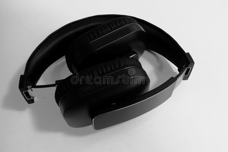 Um par de fones de ouvido sem fio dobrados da em-orelha preta no fundo branco foto de stock royalty free