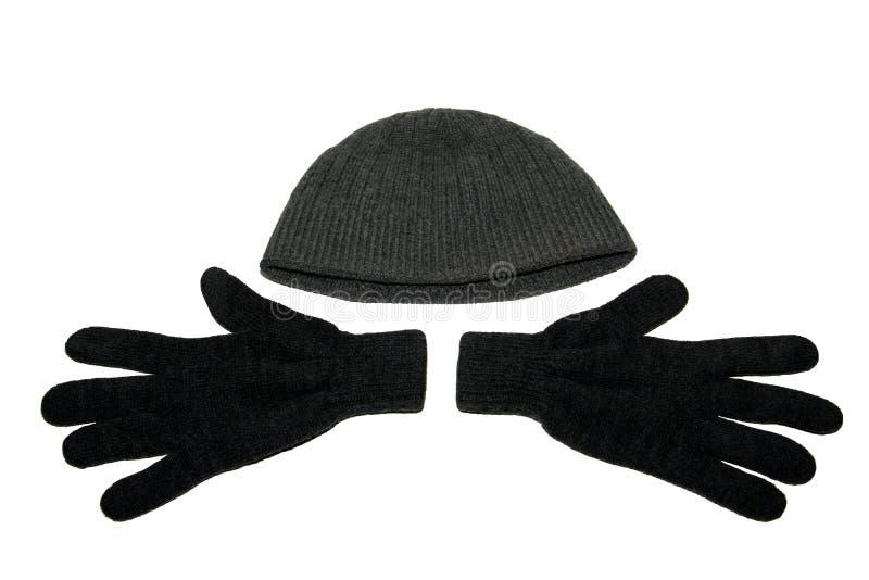 Um par de inverno cinzento fez malha luvas e um chapéu cinzento do inverno Isolado foto de stock