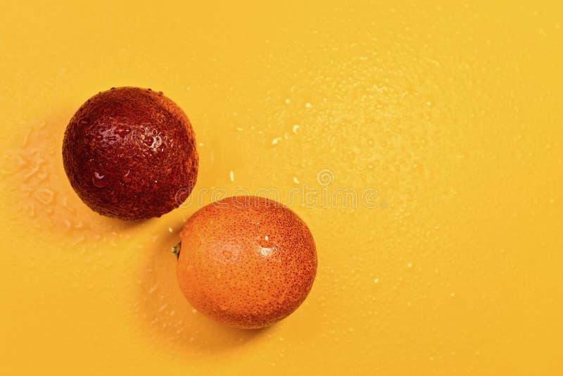 Um par de laranjas vermelhas em um fundo amarelo fotografia de stock royalty free