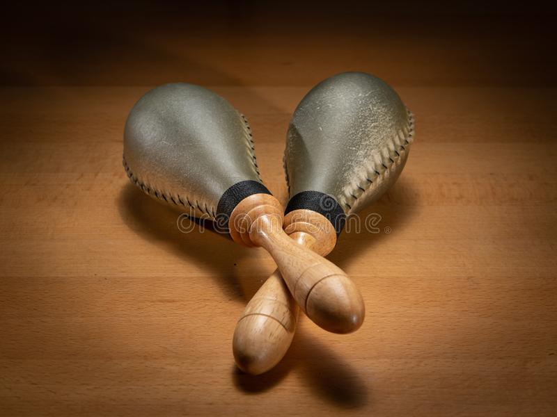 Um par de maracas do couro cru que encontram-se em uma tabela de madeira imagens de stock royalty free