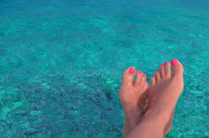 Um par de pés fêmeas em um fundo da água azul fotos de stock