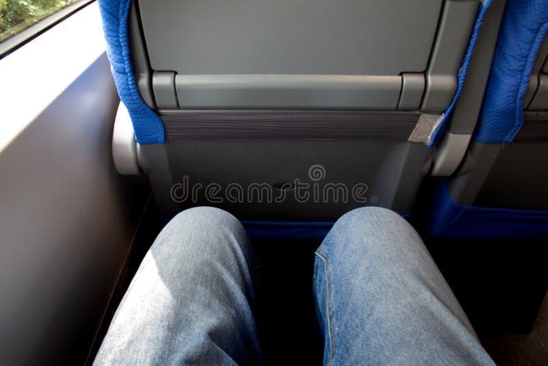 Um par de pés vestidos em cursos das calças de brim pelo trem foto de stock