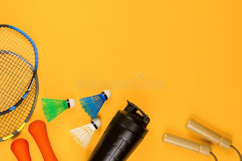 Um par de raquetes de badminton ao lado de uma garrafa de água e de algumas petecas e uma corda no fundo amarelo fotografia de stock royalty free