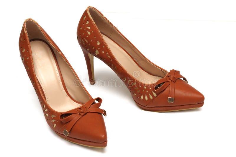 Um par de sapatas de cor castanha dos saltos altos das senhoras com uma fita da curva na parte dianteira fotografia de stock