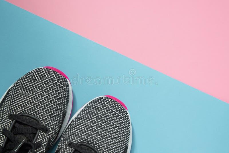 Um par de sapatas do esporte na superfície multiclored Sapatilhas preto e branco novas da mulher no rosa e no fundo pastel azul c imagem de stock royalty free