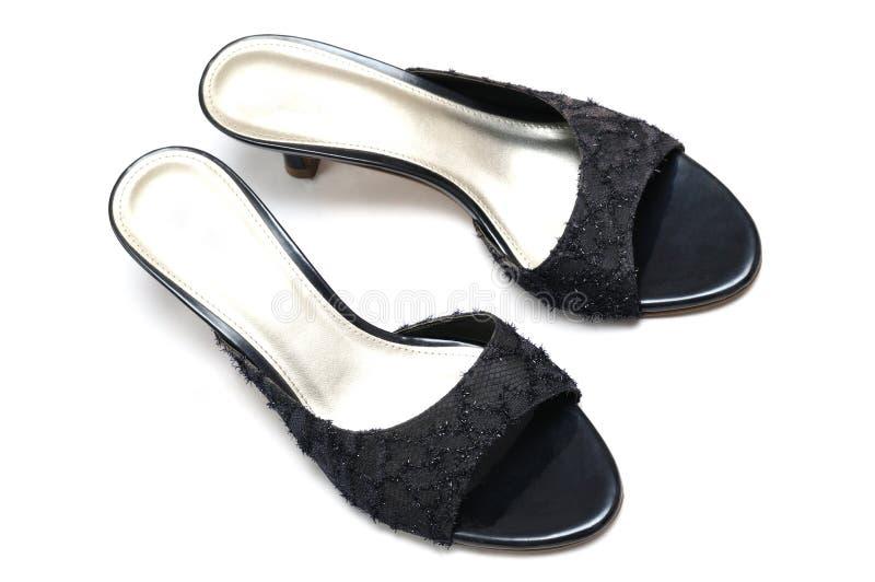 Um par de sapatas pretas dos saltos altos das senhoras com coquetes e descobre o quarto traseiro imagens de stock