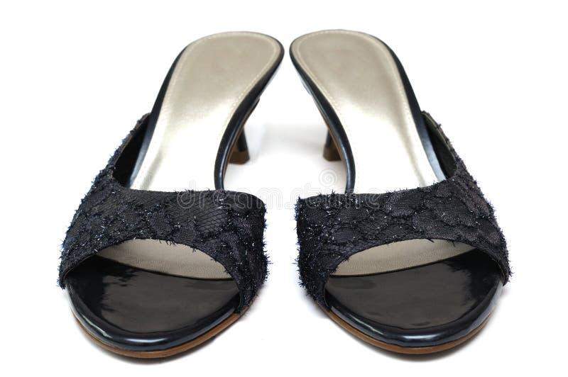 Um par de sapatas pretas dos saltos altos das senhoras com coquetes e descobre o quarto traseiro imagens de stock royalty free