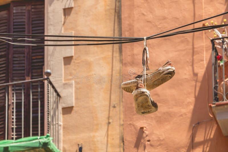 Um par de sapatas velho que penduram em um cabo bonde na altura fotografia de stock
