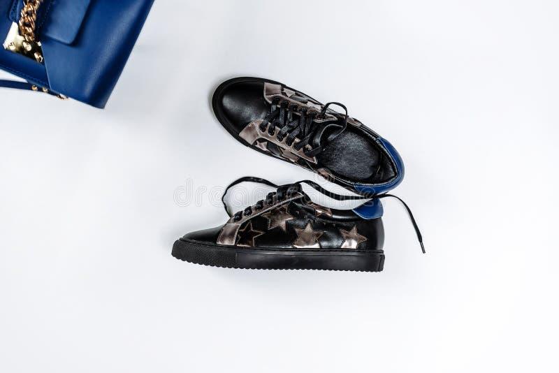 Um par de sapatilhas de couro pretas com estrelas de prata e de um saco azul com uma corrente do ouro em um fundo branco foto de stock royalty free