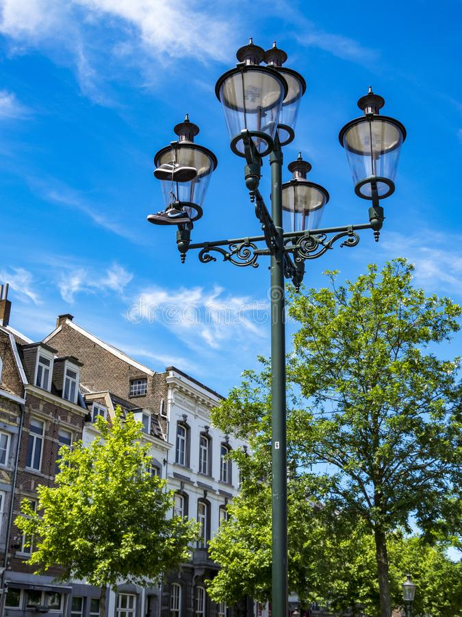 Um par de sapatilhas de Nike que penduram pelos laços de uma lâmpada de rua, uma sapata que oscila em Maastricht, Países Baixos imagens de stock royalty free