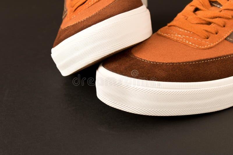 Um par de sapatilhas novas em um fundo escuro Espaço vazio do texto foto de stock royalty free