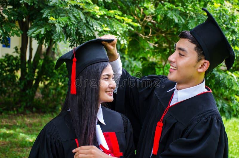 Um par do homem e da mulher vestido no vestido ou em graduados pretos da graduação com felicitações com chapéus da graduação está fotos de stock royalty free