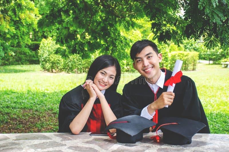 Um par do homem e da mulher vestido no vestido ou em graduados pretos da graduação com felicitações com chapéus da graduação está fotografia de stock royalty free