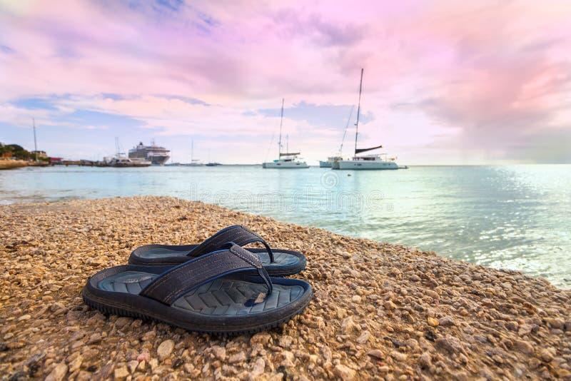 Um par dos calçados de borracha na praia na areia foto de stock