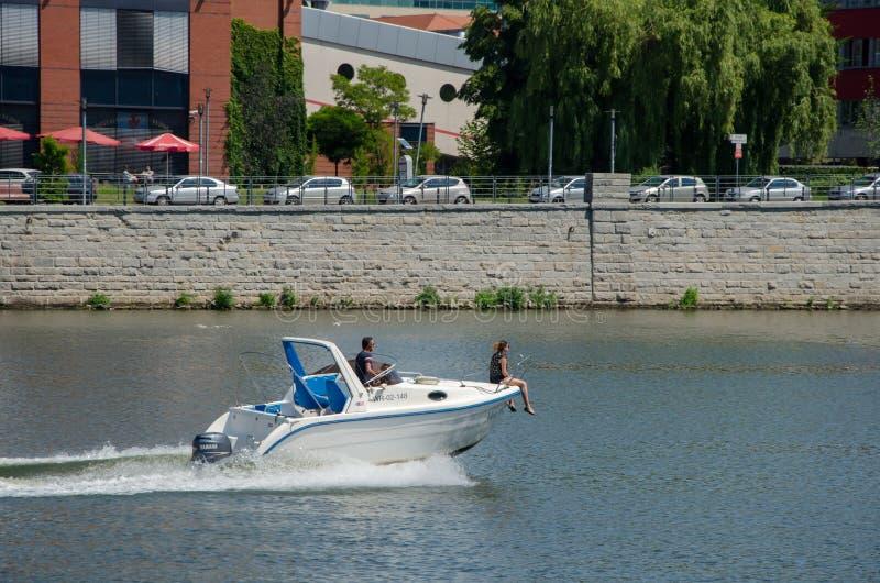Um par em um barco de motor no rio A mulher senta-se na tribuna da imagens de stock
