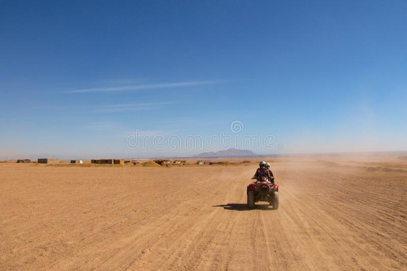 Um par em cursos do amor através do deserto em uma bicicleta do quadrilátero fotografia de stock