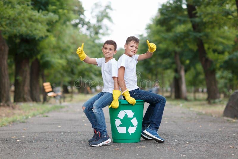 Um par escolares nas luvas amarelas do látex que sentam-se em um escaninho de reciclagem e mostrar os polegares acima em um parqu fotografia de stock