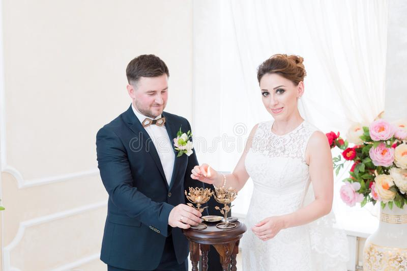 Um par feliz bonito no escritório de registro executa um ritual do casamento com a iluminação da vela imagens de stock royalty free