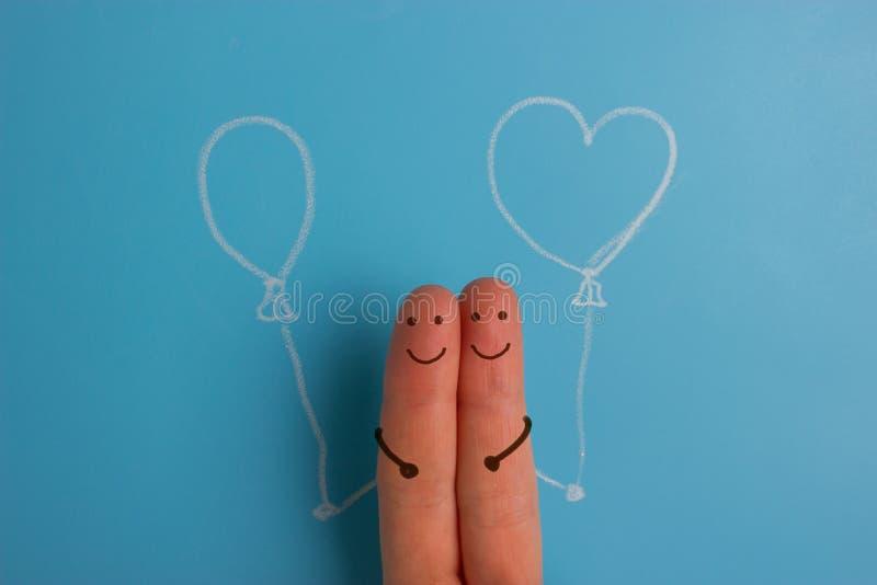 Um par feliz dos dedos no amor com smiley e aperto pintados fotografia de stock
