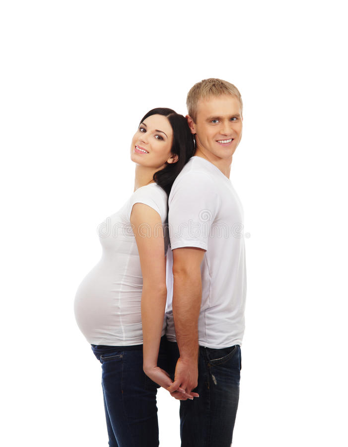 Um par feliz que espera o bebê na roupa branca imagens de stock