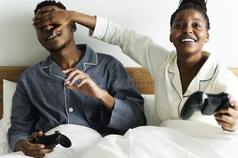 Um par feliz que joga o jogo de vídeo na cama imagens de stock royalty free