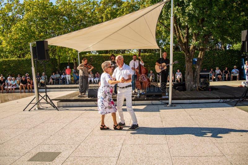 Um par idoso dança durante um concerto do ar livre foto de stock