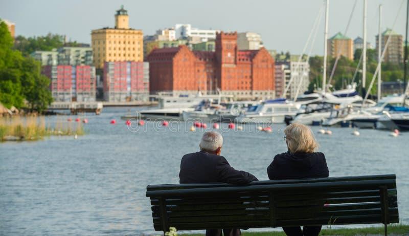 Um par idoso, um homem e uma mulher com cabelo cinzento, sentam-se em um banco pelo lago no fundo dos iate e de casas modernas fotos de stock