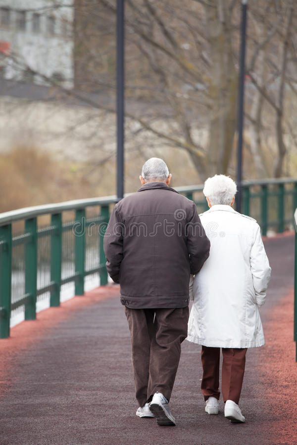 Um par idoso que anda ao longo de um trajeto Velinos cidade do La, Andorra foto de stock